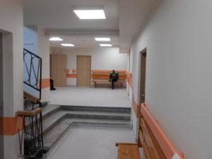 Poczekalnia poradnii po remoncie - jasne ściany z pomarańczowymi listwami odbojowymi, nowe drzwi.