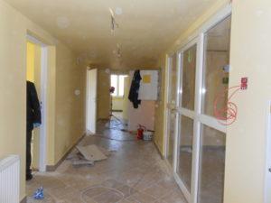 Pomieszczenia w czasie remontu - zmiana koloru ścian, skurzona podłoga i wystające kable do podłączenia nowej instalacji elektrycznej.