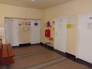 Zespół Poradni Specjalistycznych przy Al. Wolności 49 - duży korytarz, ciemna podłoga, odrapane ściany i drzwi.