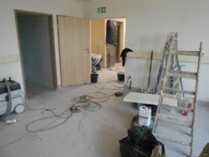 Pomieszczenia budynku Poradnii Specjalistycznych w trakcie remontu - rozłożone maszyny, drabina, malowane ściany, układanie nowych podłóg.